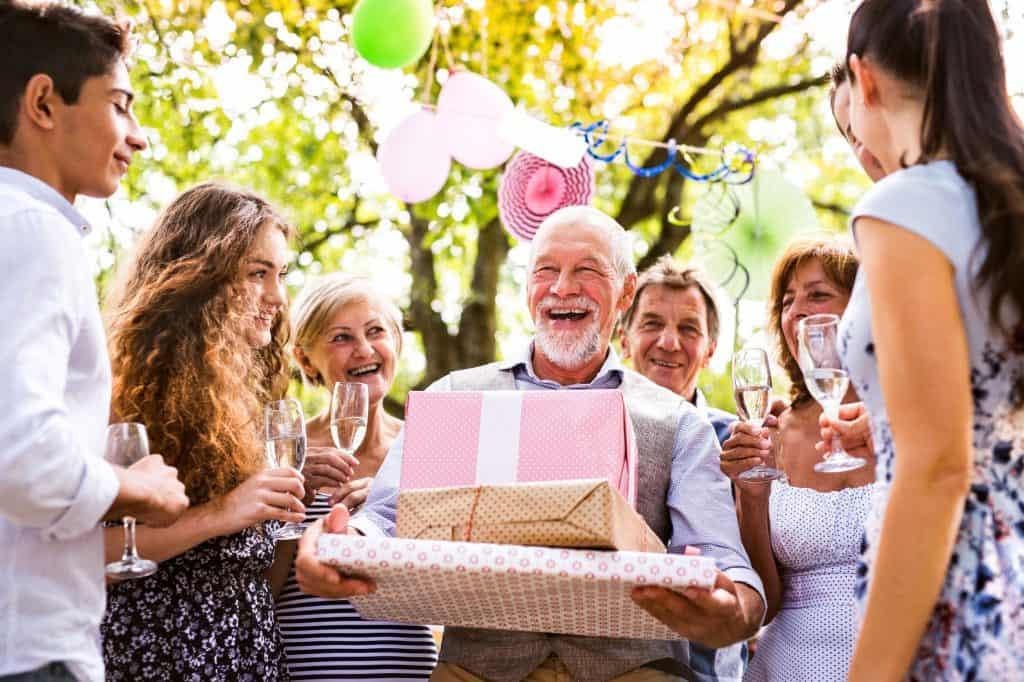 Na foto um senhor com vários presentes e pessoas ao seu redor.