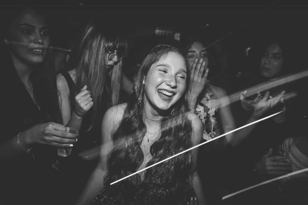 Foto preta e branco, tirada em uma balada, com destaque para uma mulher de cabelos longos, sorridente e dançando. No fundo, ao menos quatro outras mulheres também estão dançando.