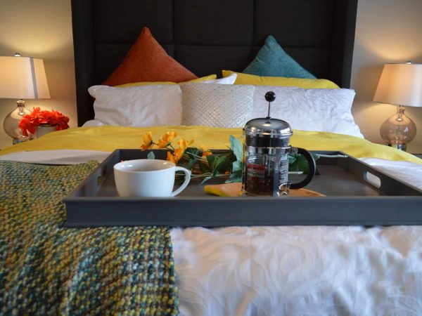 Bandeja de café da manhã apoiada aos pés da cama.