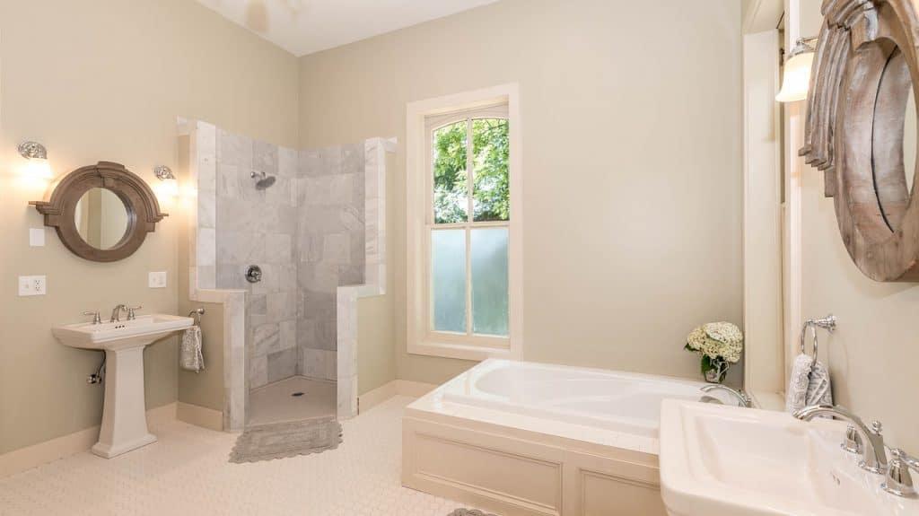 Banheiro grande com pia, banheira e box com chuveiro.