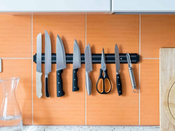 Barra magnética fixada em parede de cozinha acomoda facas, tesoura e outros utensílios.