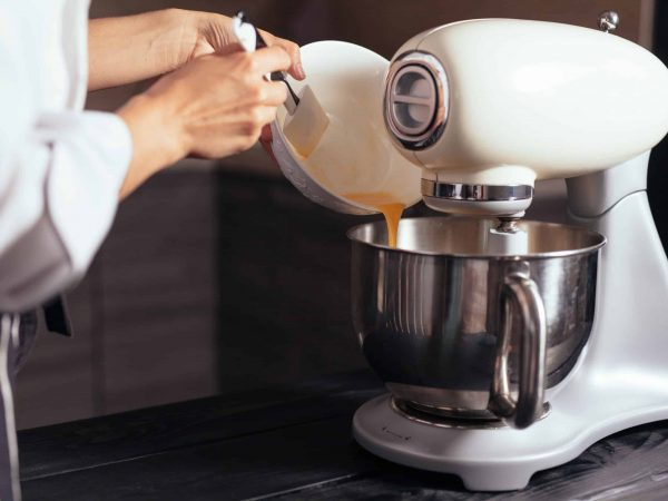 Imagem de pessoa colocando ingredientes dentro de batedeira kitchen aid.
