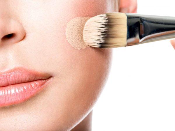 Foto que mostra as mãos de uma pessoa aplicando, com a ajuda de um pincel, maquiagem cremosa no rosto.