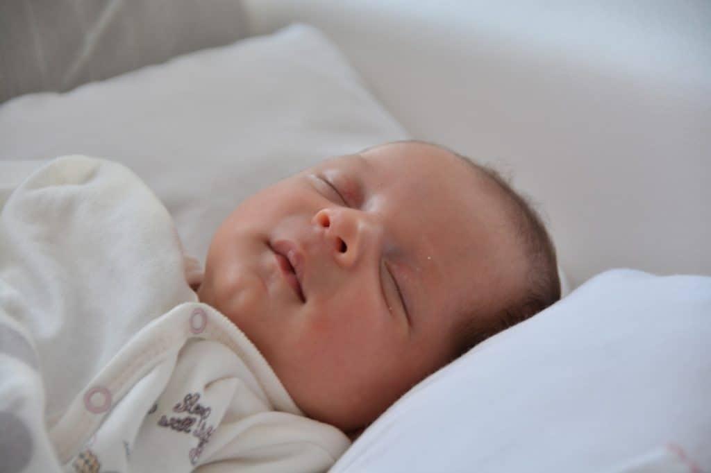 Bebê dormindo sobre travesseiro antirrefluxo.