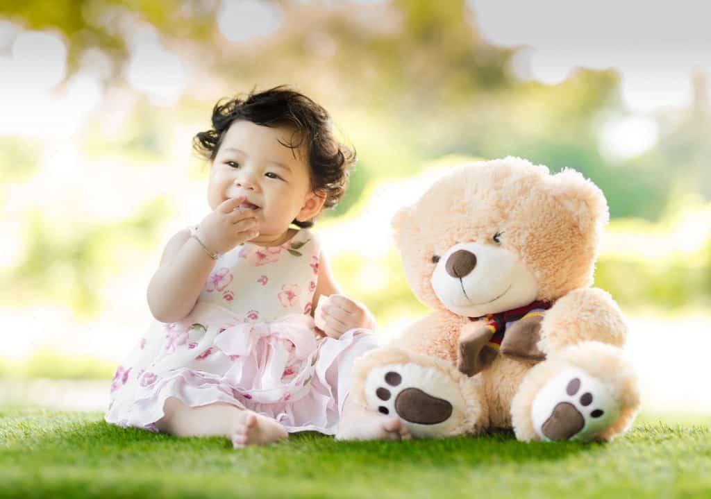 Na foto uma bebê sentada em uma grama com um ursinho ao lado.