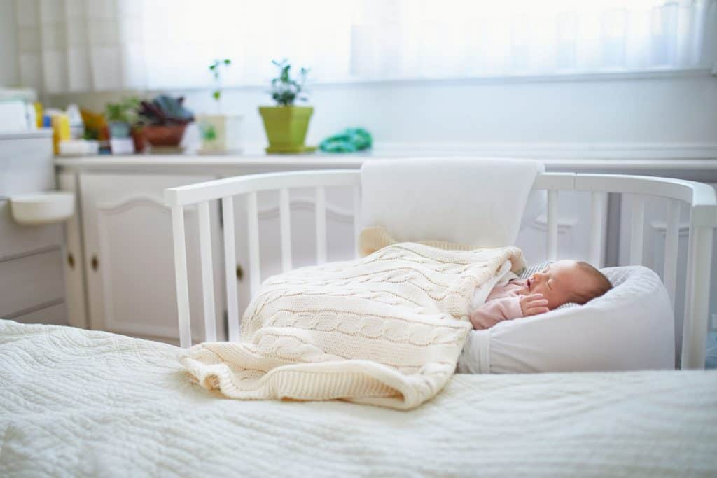 Baby sleeping in mini crib next to parents bed.
