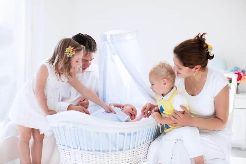Mãe, pai, filha e filho, com bebê no mini berço.