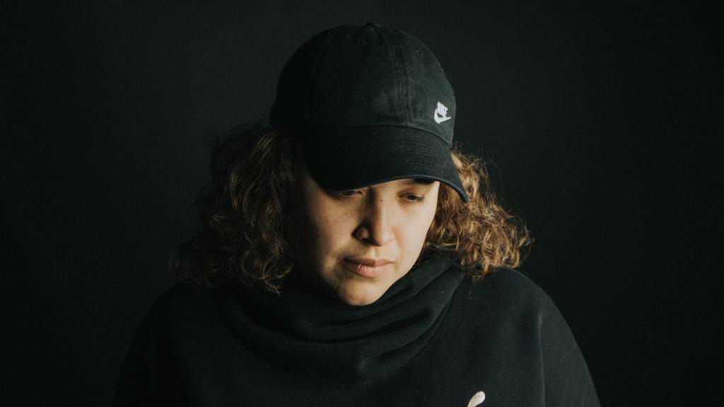 Imagem mostra uma mulher usando um boné Nike de aba curva, enquanto olha para baixo. Quase não dá para distinguir o fundo escuro de seus trajes, também escuros.