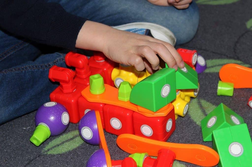 Na foto uma criança com um brinquedo de encaixar.