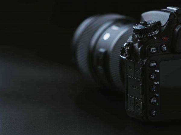 Na foto uma câmera digital em foco com um fundo preto.