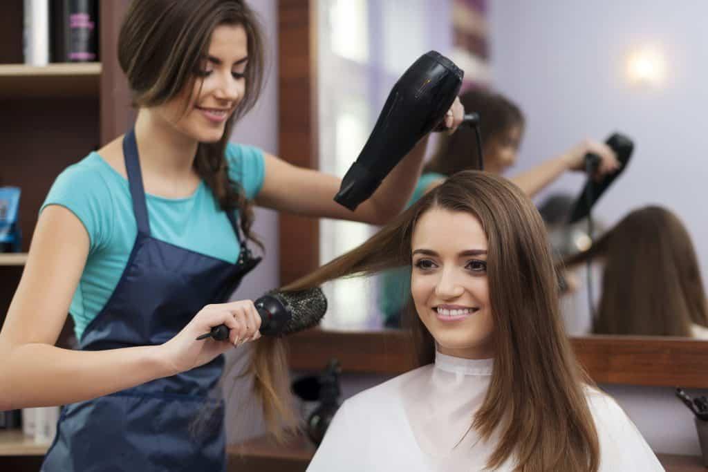 Imagem de uma cabeleireira fazendo escova no cabelo de uma cliente.
