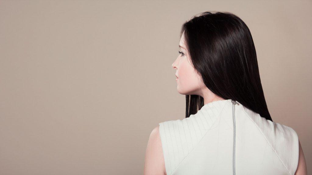 Foto de uma mulher de cabelo preto liso, de costas, olhando para o lado.
