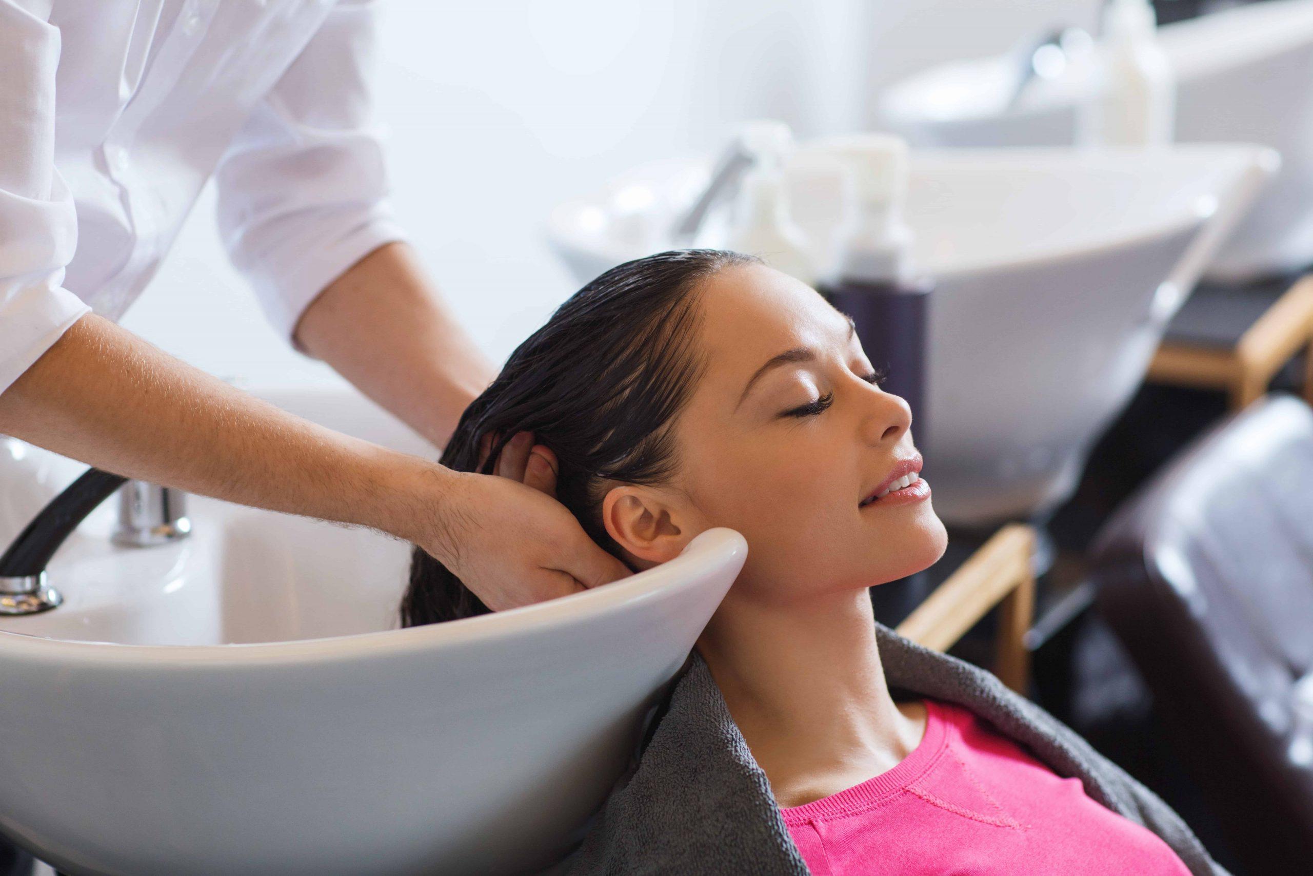 Moça tendo o cabelo lavado em lavatório de salão.