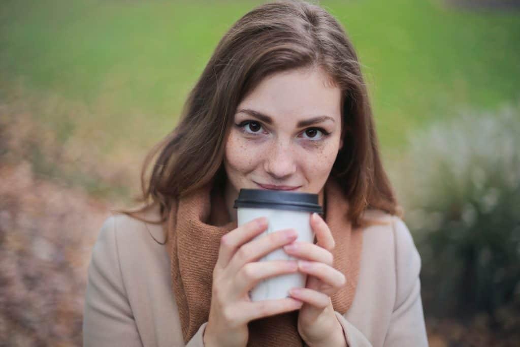 Imagem de uma moça tomando café em um copo descartável.