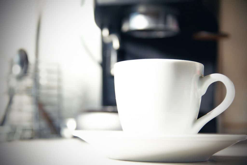 Na foto uma xícara de café branca com uma cafeteira no fundo.