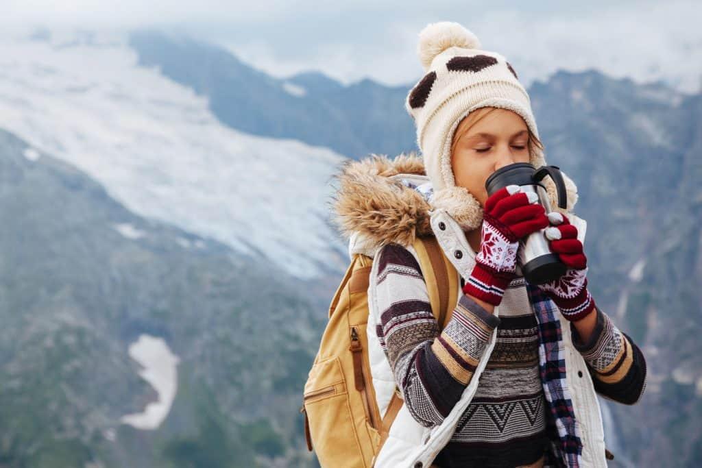 Mulher agasalhada em montanha com neve bebendo café em copo térmico.