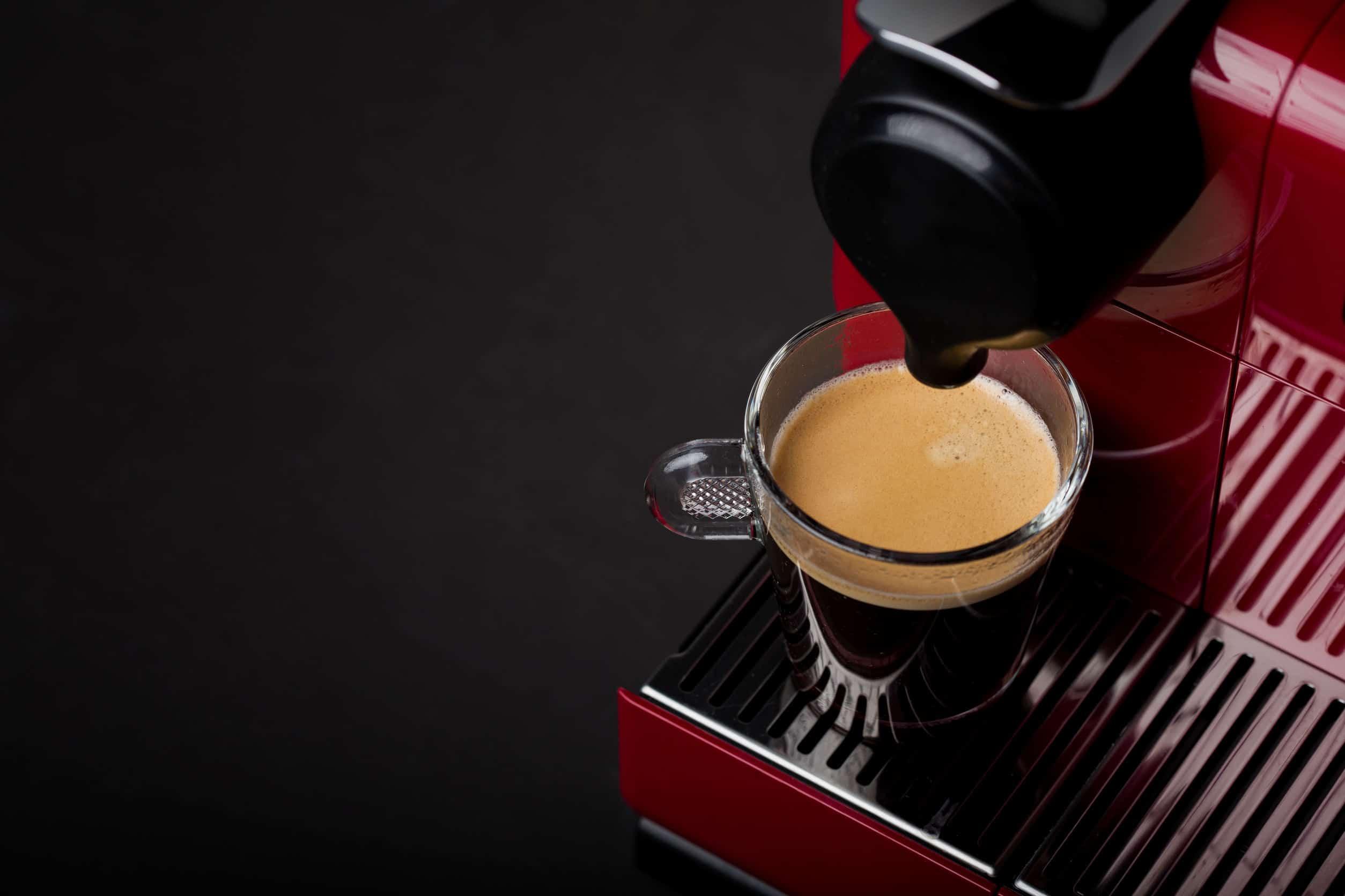 Na foto uma cafeteira vermelha com detalhes em preto e uma xícara transparente cheia de café.