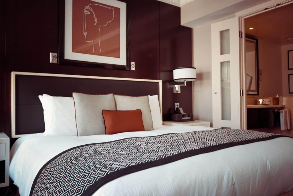 Foto mostra uma cama com roupas de cama lisas, almofadas e uma manta estampada. Ela tem uma cabeceira escura. Acima dela, há um quadro. Do lado, um criado-mudo e uma luminária de parede.
