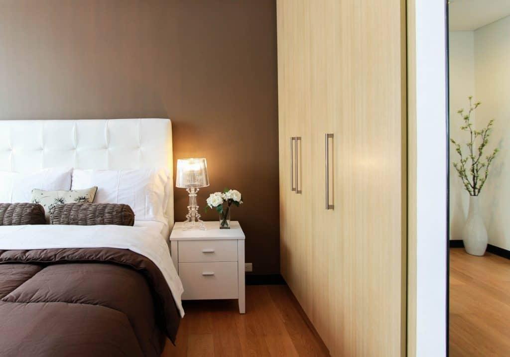 Na foto um quarto com uma cama com cabeceira branca, um criado-mudo ao lado e um guarda-roupa.