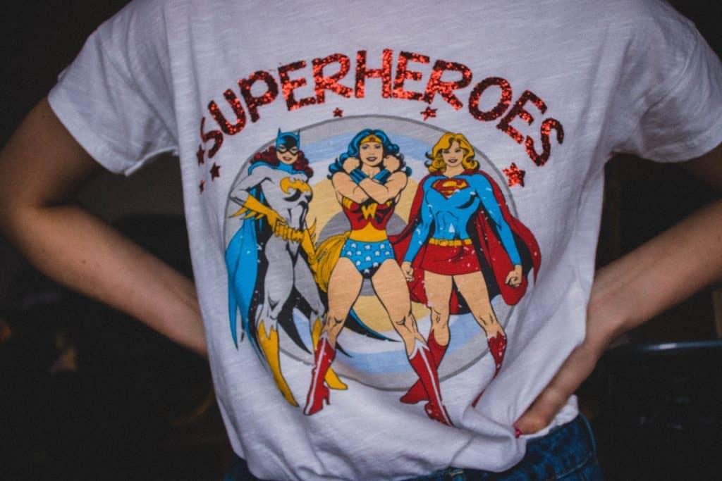 Na foto uma mulher com uma camiseta de super-heróis.