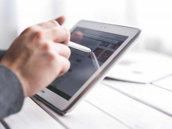 Na foto as mãos de uma pessoa usando um tablet com uma caneta em cima de uma mesa de madeira branca.