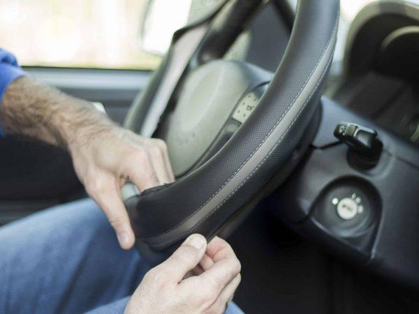 Um homem coloca a capa em um volante de um carro.
