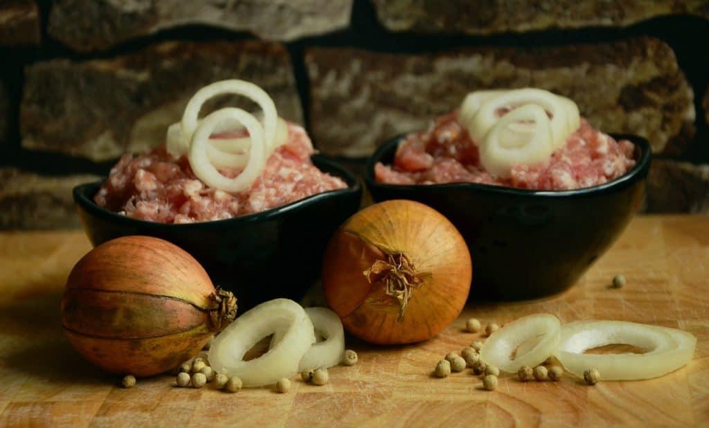 Na foto duas vasilhas com carne moída com cebolas e grãos de pimenta ao redor.