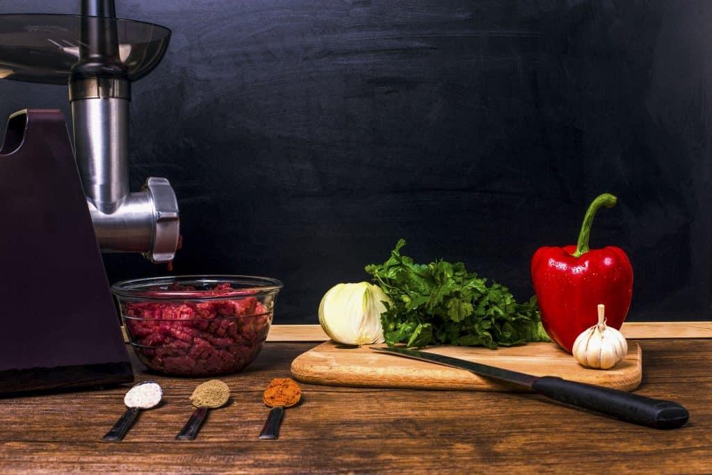 Na foto um moedor de carne elétrico ao lado de uma tábua com legumes e três colheres com tempero.