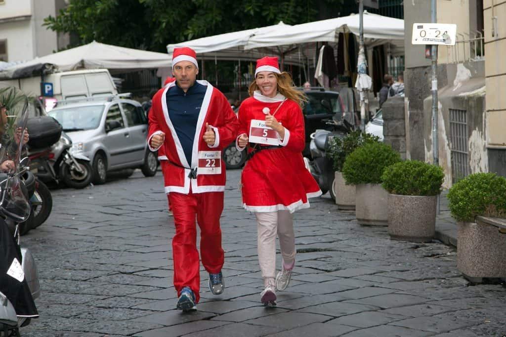 Casal corre vestido de papai e mamãe Noel