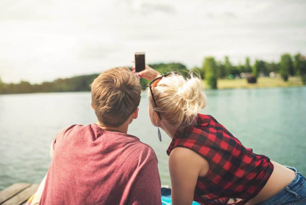 Imagem mostra um casal tirando selfie em um lago.