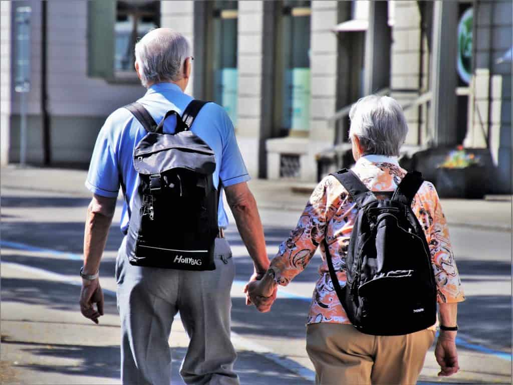 Casal idoso de mãos dadas e mochila nas costas.