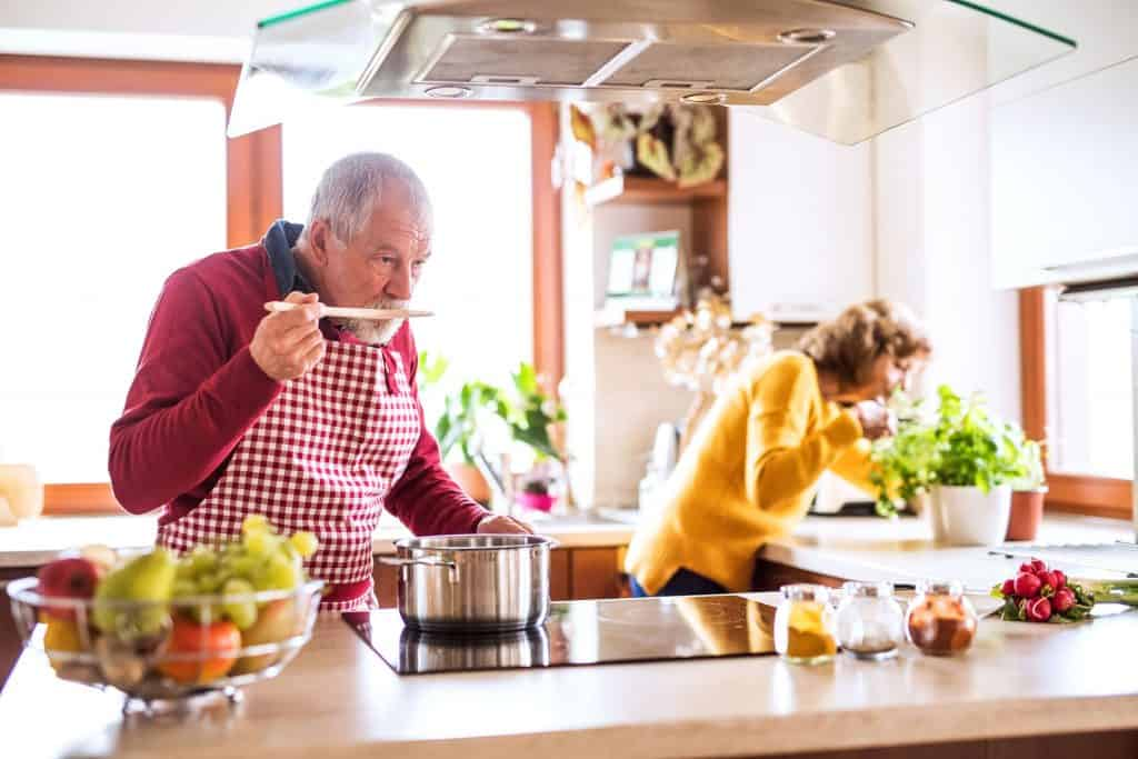 Imagem de um casal idoso cozinhando juntos na cozinha com bancada de ilha.