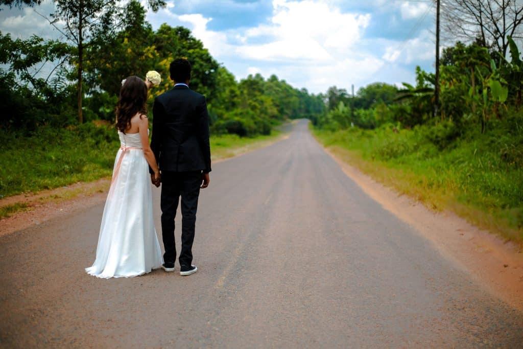 Na foto um casal de noivos em uma estrada vazia.
