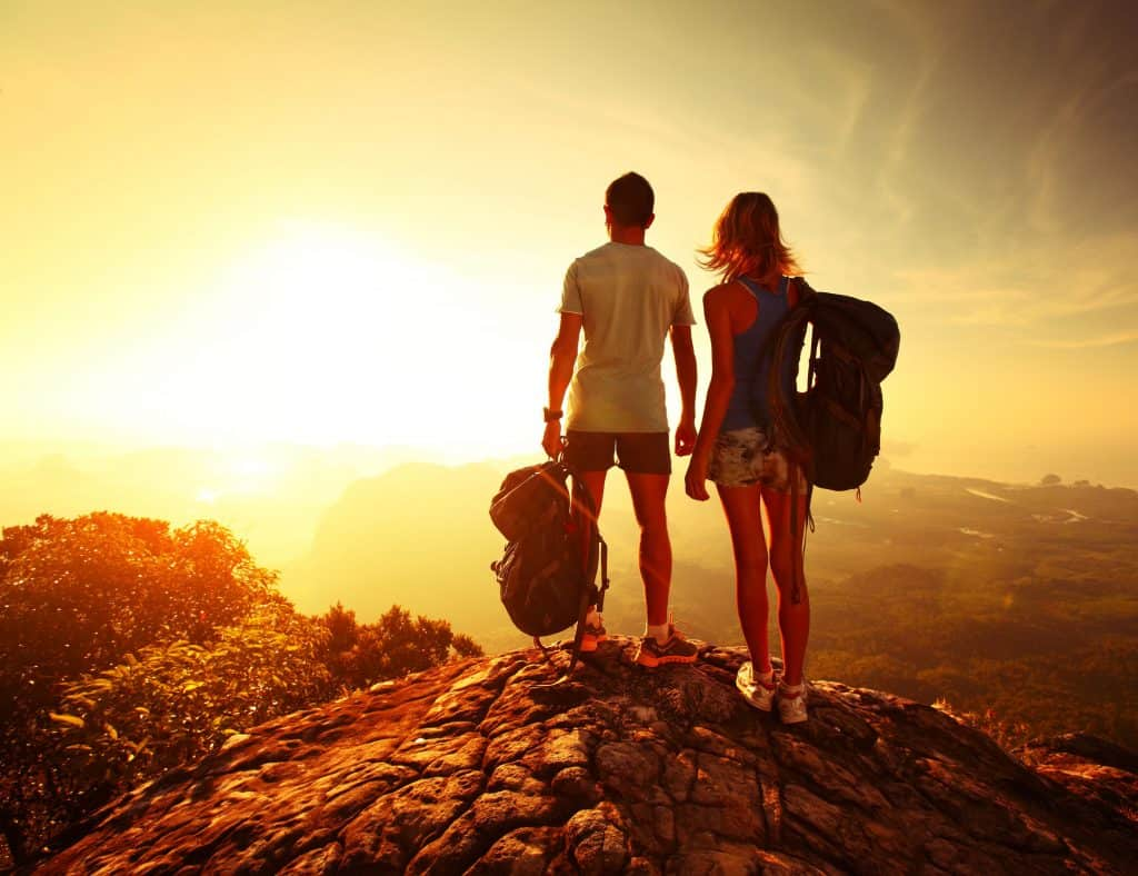 Casal com mochila cargueira observando por do sol.