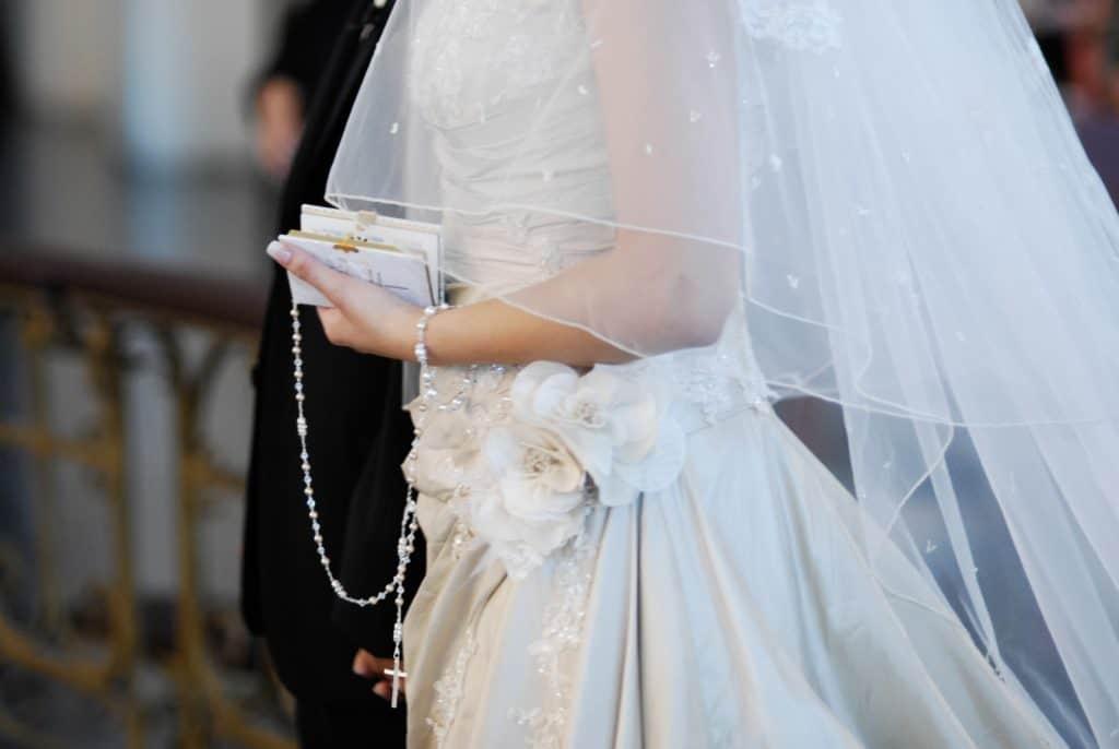 Imagem de noiva segurando um terço branco.