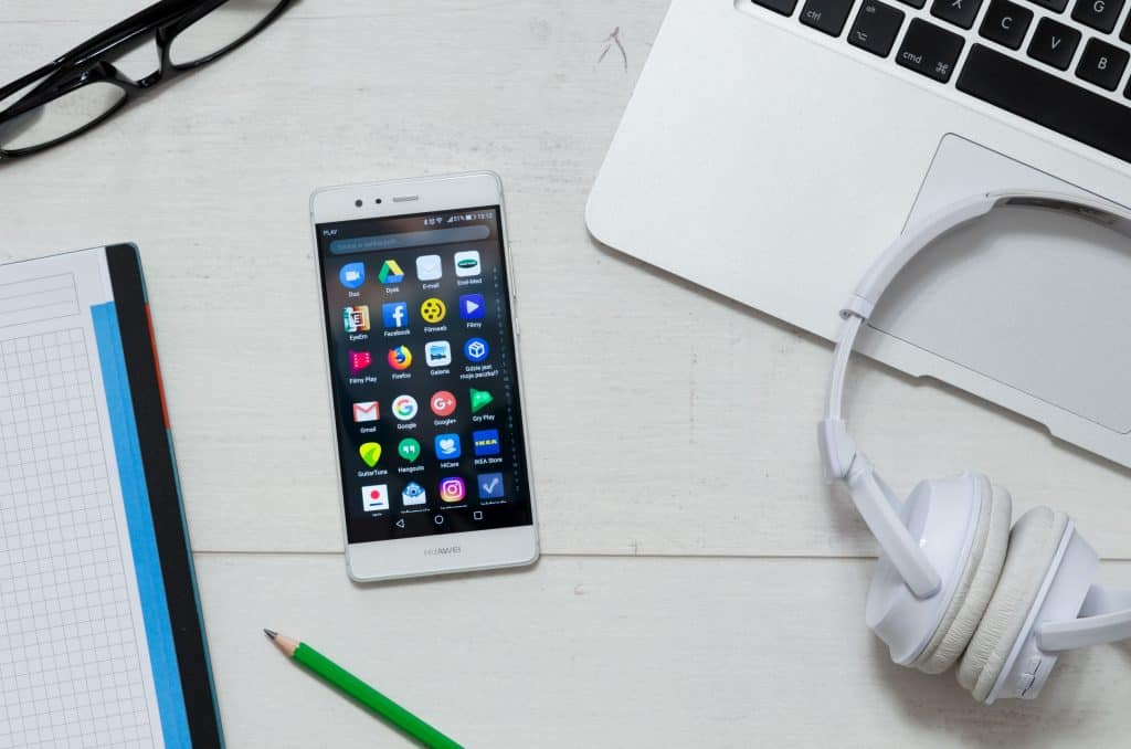 Na foto um celular Huawei ao lado de um computador, fone de ouvido, óculos, papel e lápis.