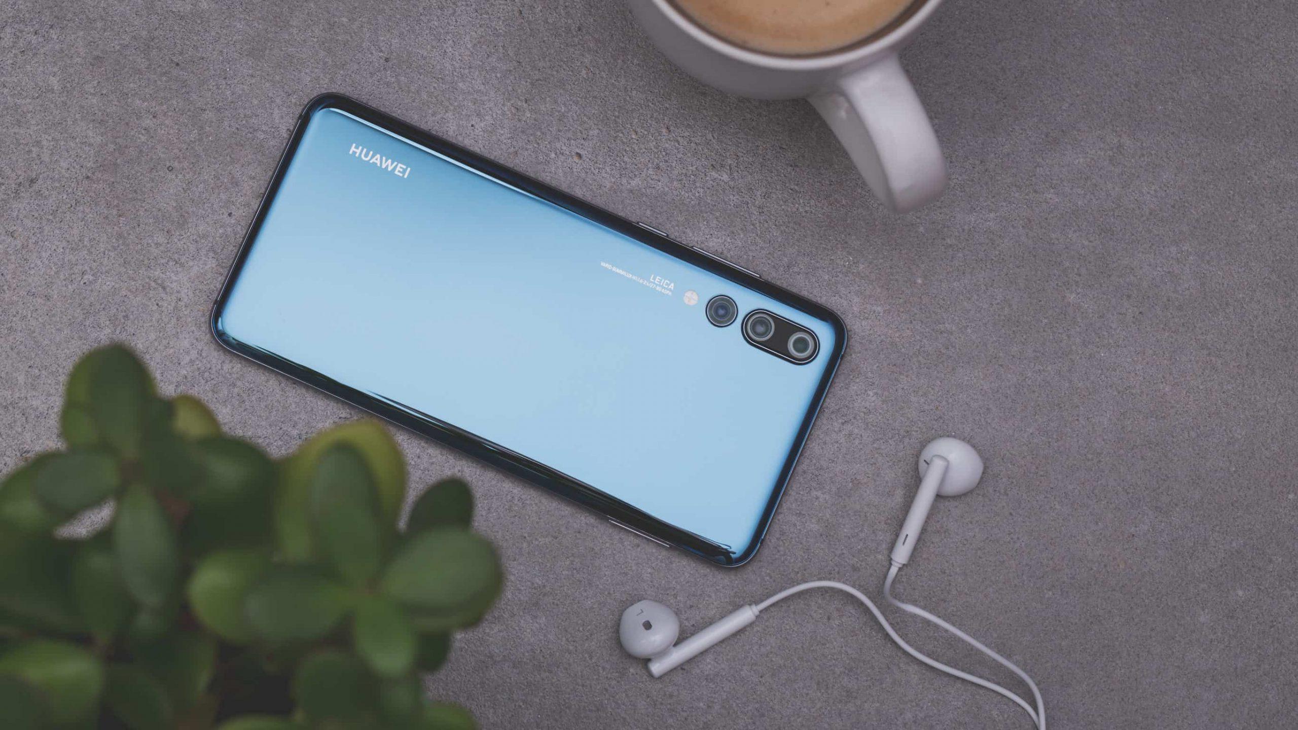 Na foto um celular Huawei com fones de ouvido e uma caneca ao lado.