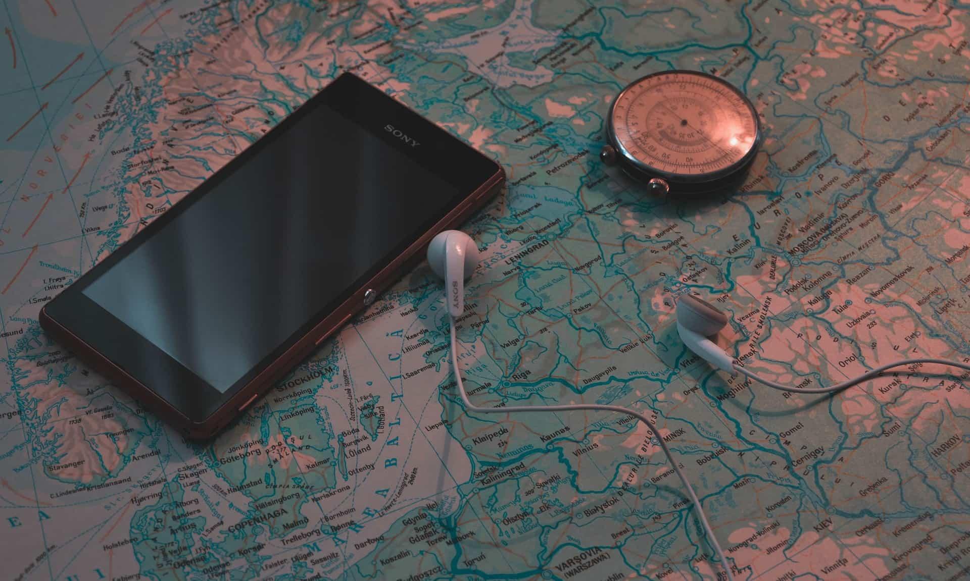 Imagem mostra um celular Sony preto e um fone de ouvido branco em cima de um mapa mundi.