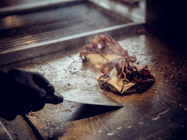 Na foto dois hambúrgueres em uma chapa e a mão de uma pessoa segurando uma espátula.