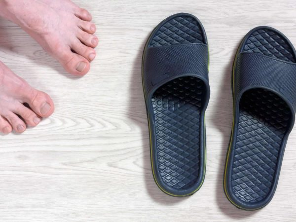 Male bare feet next to a pair of blue flip-flops on a white wooden floor