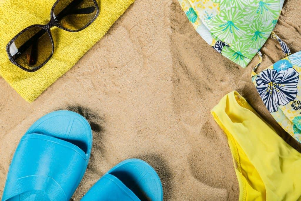 Imagem com fundo de areia e em cima parte de biquíni, óculos escuro e chinelo.