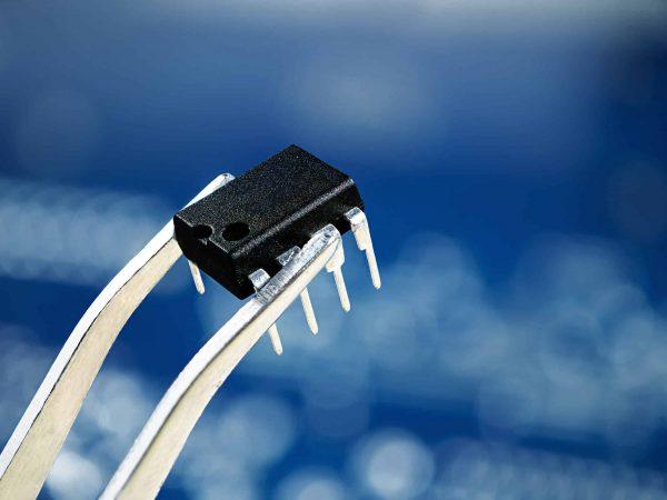 Na foto um circuito integrado sendo segurado por uma pinça.