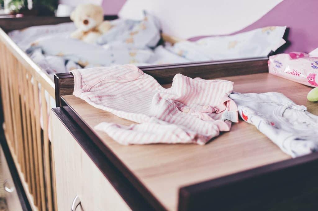 Na foto um quarto de bebê com alguns bodies em cima da cômoda.