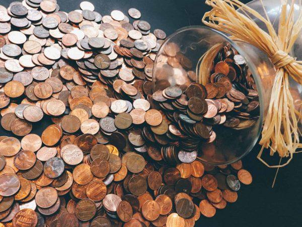 Imagem mostra um grande número de moedas ao lado de um pote virado.