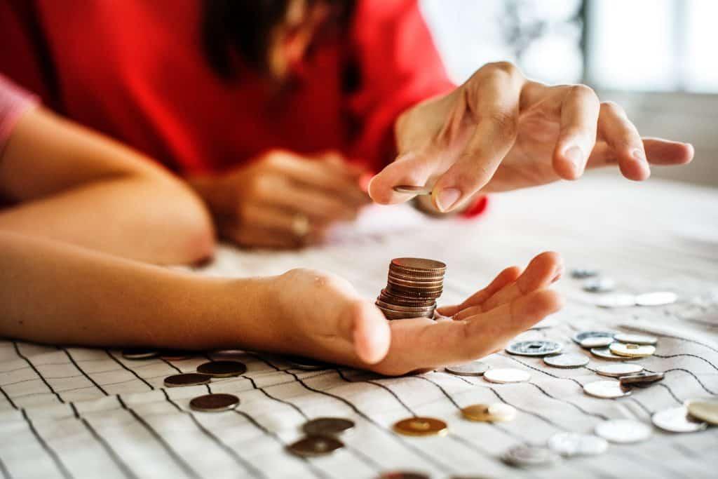 Imagem mostra duas pessoas contando moedas manualmente.