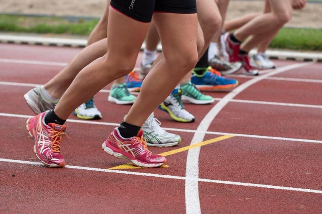 Foto das pernas de várias pessoas correndo em uma pista de corrida. O destaque se dá para a pessoa mais próxima da câmera, que use meia preta e tênis rosa com laranja.
