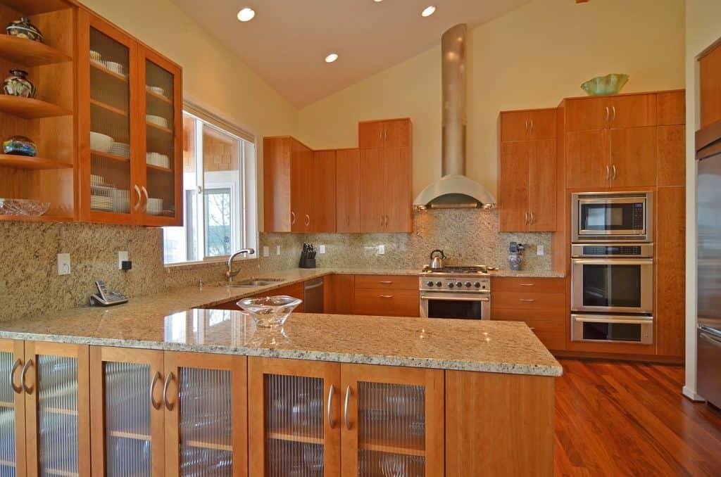 Imagem de cozinha com móveis de madeira e coifa de parede sobre fogão.