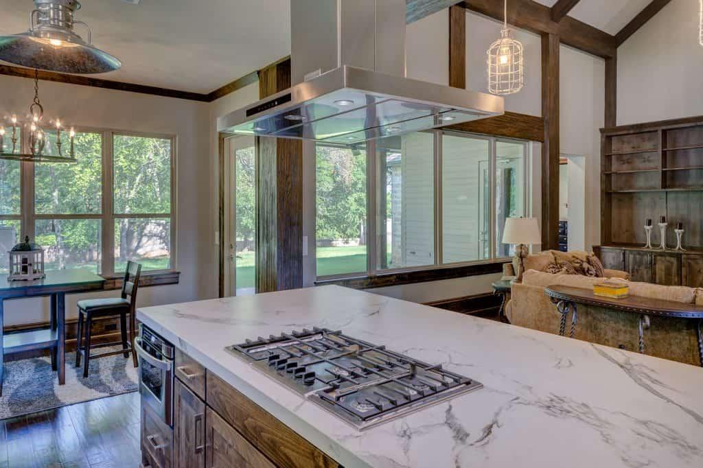 Imagem de cozinha com ilha de pedra e fogão embutido com coifa de teto.