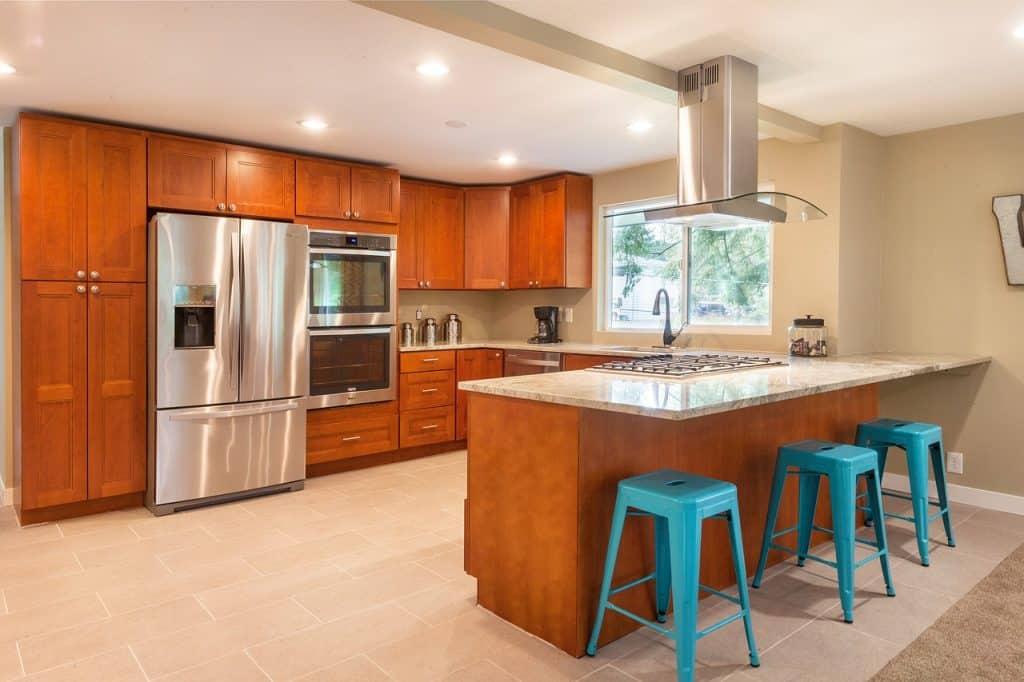 Imagem de cozinha com móveis de madeira e coifa de teto sobre ilha com fogão embutido.