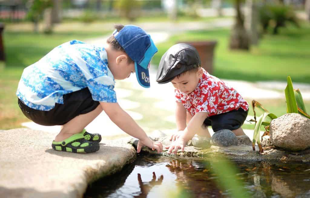 Na foto dois meninos na beira de um lago olhando para a água.